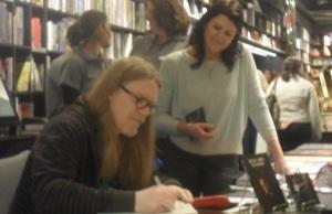 Junto a Beth da Livraria Vanguarda, 1berto firma o livro de assinaturas da loja